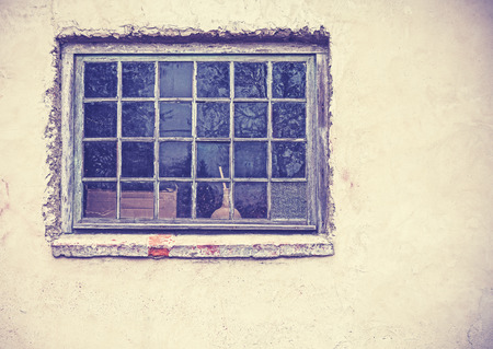 Old grungy window on an old dirty wall, retro filtered. photo