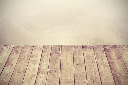 Retro stylized picture of wooden boards and lake, background with space for text. photo