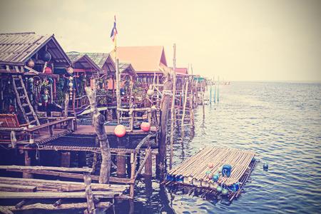 dwelling: Retro stylized houses on water, settlement on Lanta Island, Thailand. Stock Photo
