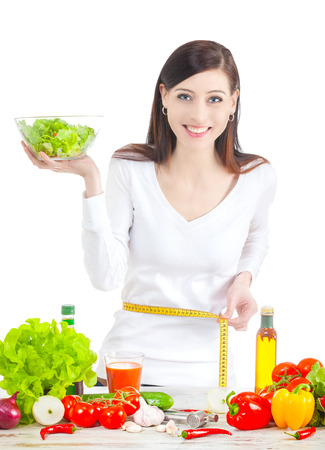 waistline: Young happy woman with salad, measuring her waistline. Healthy food ans lifestyle concept.