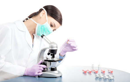 isolated white: Female doctor or scientific researcher in mask using pipette and microscope, space for text.