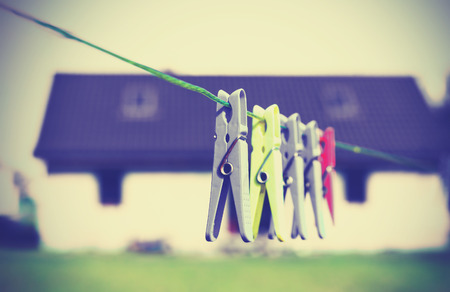 county side: Retro filtered clothespins hanging on a cord in front of house, concept photo. Stock Photo