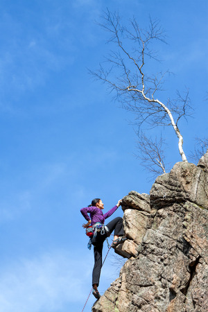 steep cliff: Female happy rock climber on a steep cliff. Stock Photo