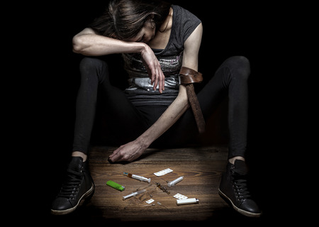 Young woman poses as drug addict, concept photo against black wall. Strong contrast and texture to strengthen message. Stock Photo