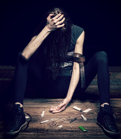 Grunge cross vintage filtered photo of a woman posing as drug addict Stock Photo
