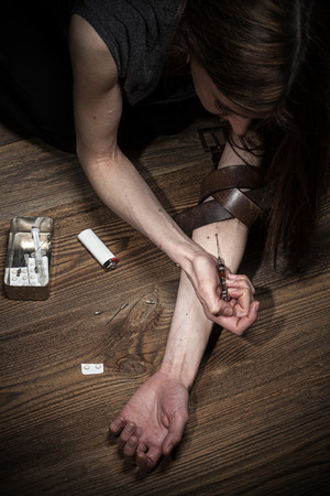 strong message: Young woman poses as drug addict, concept photo. Strong contrast and texture to strengthen message. Stock Photo