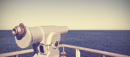 to foresee: Retro vintage toned photo of a telescope on a pier pointed at horizon, future concept.