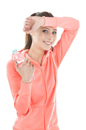 Portrait of a young beautiful smiling woman holding bottle in tracksuit, isolated on white. Stock Photo