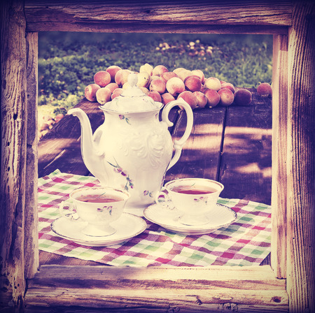 tea set: Vintage toned tea set in garden in wooden frame.