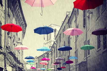 lluvia paraguas: Vendimia Retro filtra sombrillas de colores que cuelgan encima de la calle de Ferrara, fondo blanco y negro.