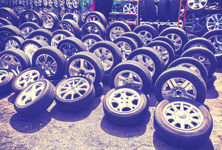 aluminum wheels: Vintage style picture of car wheels and aluminum rims on the street. Stock Photo