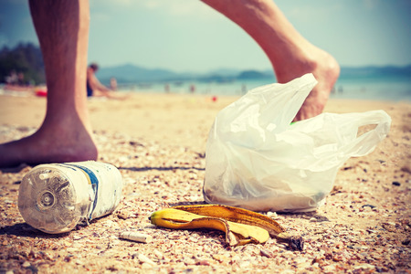 Vintage  style picture of garbage left by tourists on a beach, environmental pollution concept picture. Standard-Bild