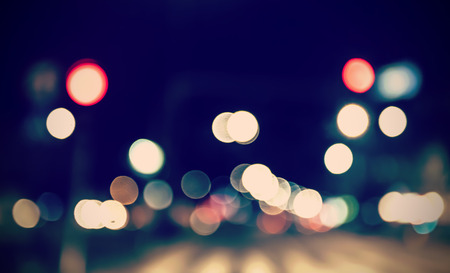 Retro toned blurred street lights, urban abstract background.