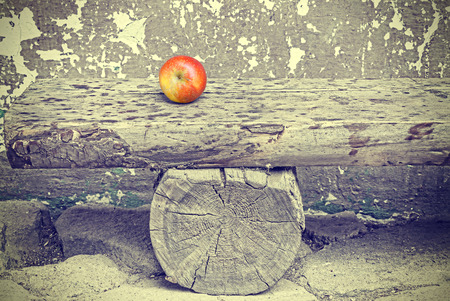 time passing: Ripe apple on old wooden bench, retro toned time passing and aging concept.