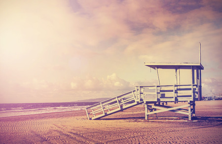 Vintage filtered picture of wooden lifeguard tower at sunset, beach in California, USA.