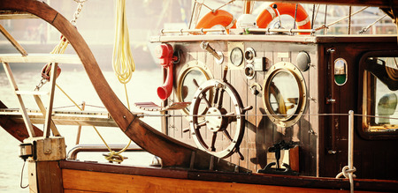 wheelhouse: Retro vintage filtered photo of old sailing boat bridge with wooden steering wheel.