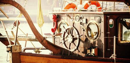wheelhouse: Retro vintage filtered photo of old sailing boat bridge with wooden steering wheel.