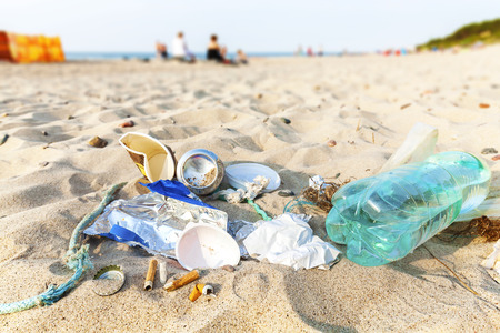 Garbage on a beach left by tourist at sunset, environmental pollution concept picture, baltic Sea coast, Dziwnowek in Poland. Stockfoto