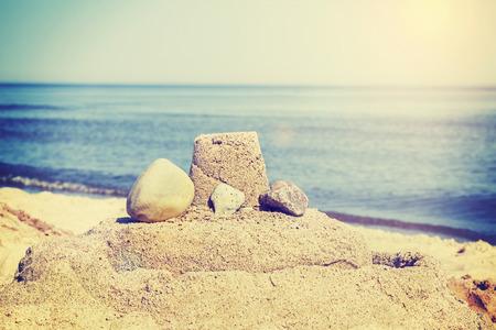 sandcastle: Vintage retro toned simple sandcastle on a beach, summer holidays concept.