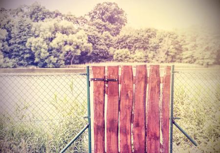 garden gate: Retro toned wooden garden gate and wire fence.