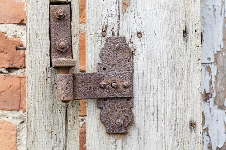 hinge: Rusty hinge on old wooden door, rustic background.