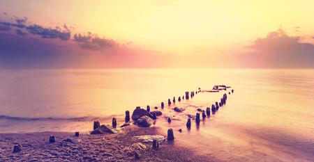紫の日没後穏やかな海を風景します。