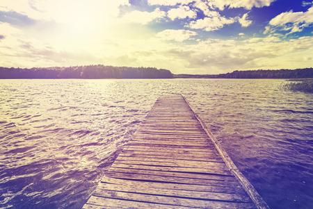 peaceful background: Vintage toned photo of beautiful sunset over lake, Ostromecko in Poland.