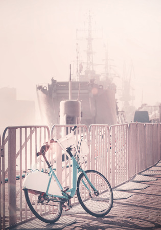 effect sunset: Vintage toned bicycle parked by pier with ship in a distance, sunset lens flare effect.