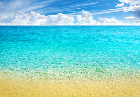 Summer beach background, clear water and blue cloudy sky.