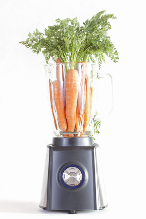 cocktail mixer: Electric blender with carrots on a white background.