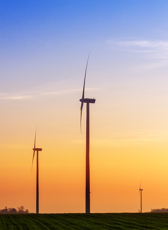 industrial landscape: Alternative energy concept, windmills at sunset.