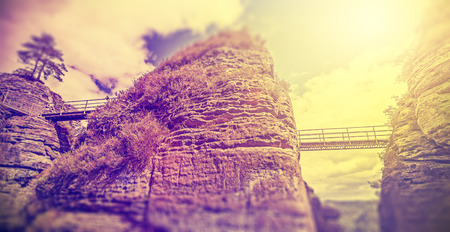 tilt: Vintage filtered bridges between rocks, concept photo with tilt shift effect.