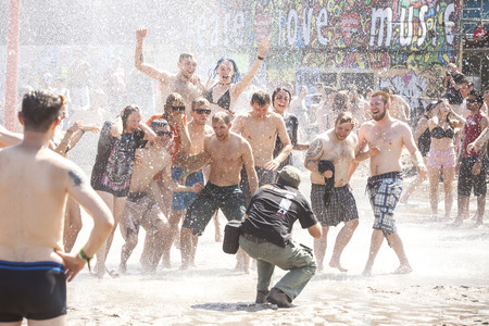woodstock: Kostrzyn nad Odra, Poland - August 1, 2015: Photographer taking picture of people playing in mud during 21th Woodstock Festival Poland (Przystanek Woodstock), one of the biggest view open air festivals in Europe.