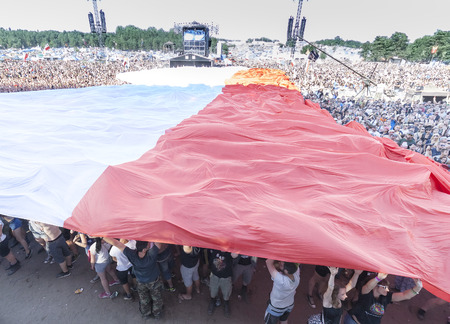 woodstock: Kostrzyn nad Odra, Poland - August 1, 2015: Polish flag spread with audience to commemorate the 71st anniversary of the Warsaw Uprising, during 21th Woodstock Festival Poland (Przystanek Woodstock).