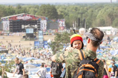 woodstock: Kostrzyn nad Odra, Poland - August 1, 2015: Man holding little child during the 21th Woodstock Festival Poland, one of the biggest open air festivals in Europe.
