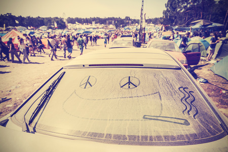 woodstock: Kostrzyn nad Odra, Poland - August 1, 2015: Funny drawing on dust covering car at the 21th Woodstock Festival Poland, one of the biggest ticket free rock music festivals in Europe, vintage toned. Editorial