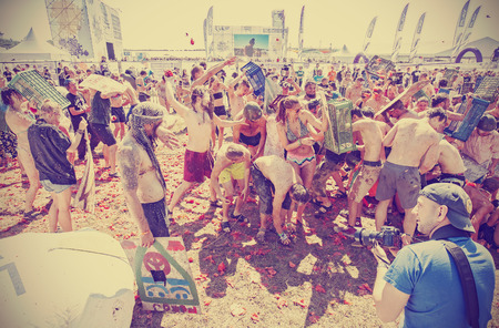 woodstock: Kostrzyn nad Odra, Poland - August 1, 2015: Tomato fight on the 21th Woodstock Festival Poland (Przystanek Woodstock), one of the biggest ticket free rock music festivals in Europe, retro toned.
