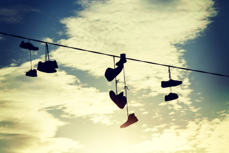 cable tangle: Vintage toned silhouettes of shoes hanging on cable at sunset. Stock Photo