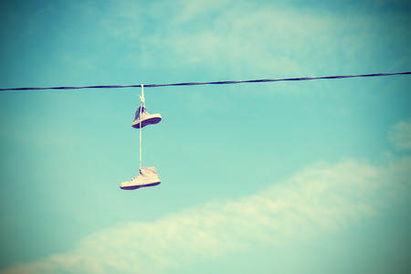 shoe strings: Retro style old shoes hanging on an electric cable, old film and vignetting effect.