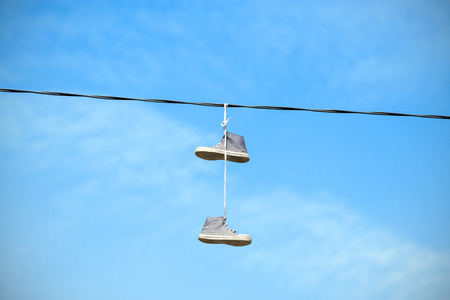 old shoes: Old shoes hanging on an electric cable against blue sky.