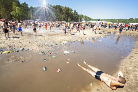 woodstock: Kostrzyn nad Odra, Poland - August 1, 2015: Young man resting at the mud pool during 21th Woodstock Festival Poland (Przystanek Woodstock), one of the biggest open air festivals in Europe.