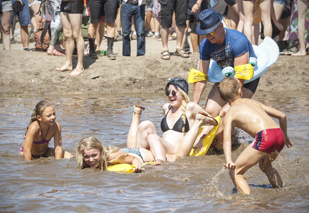 woodstock: Kostrzyn nad Odra, Poland - August 1, 2015: People playing with children in mud pool during 21th Woodstock Festival Poland (Przystanek Woodstock), one of the biggest open air festivals in Europe. Editorial