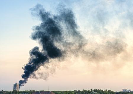 Rookpluim van een brand boven de stad bij zonsondergang. Stockfoto