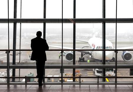 Londen, Verenigd Koninkrijk - 14 augustus 2015: Silhouet van een reiziger te wachten op een vliegtuig op de luchthaven Heathrow vertrek hal op een regenachtige dag. Stockfoto - 45565547