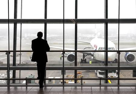 airport business: London, UK - August 14, 2015: Silhouette of a traveler waiting for a plane at the Heathrow airport departure hall on a rainy day. Editorial