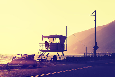 retro couple: Vintage filtered sunset over beach with lifeguard tower, Pacific Coast Highway, USA.
