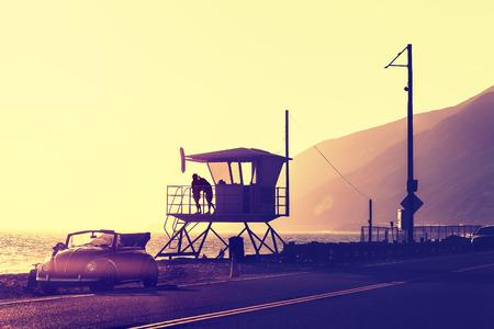 Vintage gefilterd zonsondergang over strand met badmeester toren, Pacific Coast Highway, USA.