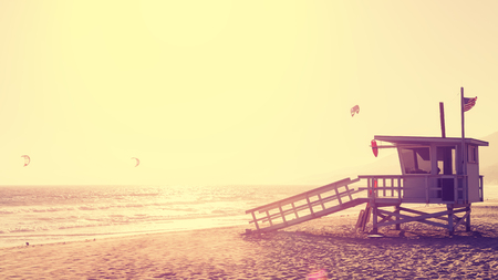 effect sunset: Vintage style picture of lifeguard tower at sunset in Malibu, lens flare effect, USA.