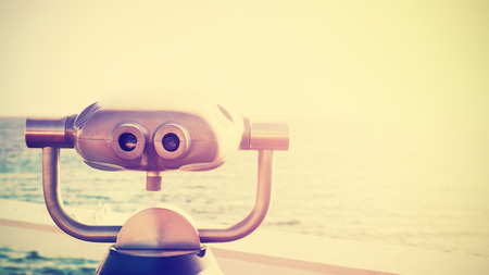 to foresee: Vintage toned photo of a binocular pointed at horizon, future concept, copy space.