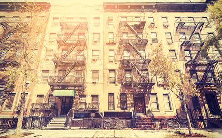 Old film retro style photo of New York building with fire escape ladders, USA. Stock Photo